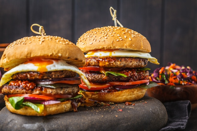 Homemade pork burgers with egg, sauce and vegetables on dark background. Premium Photo