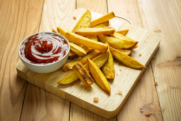 Homemade potato fries on wooden table Free Photo