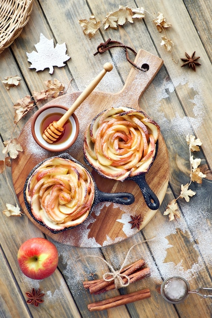 Homemade puff pastry with rose shaped apple slices baked in iron skillets on wood Premium Photo