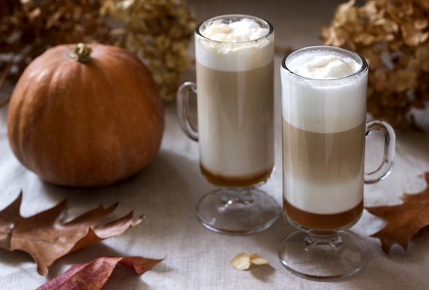 best keto sweet treats - Homemade pumpkin latte in tall glasses and pumpkin on a linen tablecloth. rustic style. Premium Photo