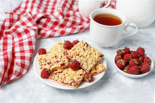Homemade raspberry crumble bar on plate on light Free Photo