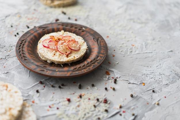 Homemade round puffed rice cake garnish with slices of turnip and cheese Free Photo
