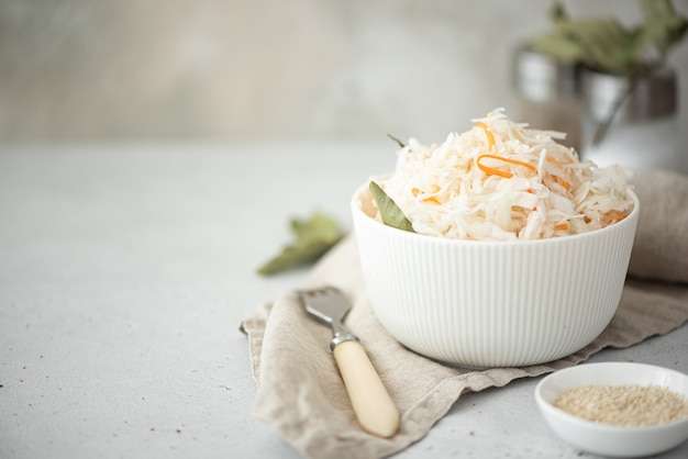Homemade sauerkraut with carrots and bay leaves in a white bowl Premium Photo