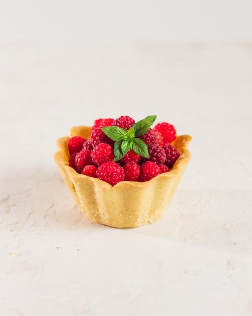 Домашнее песочное малиновое тесто. мини-тарталетки «летние ягоды» с ванильным заварным кремом и листьями мяты. свежие десерты на белом фоне изолированы. бесплатная копия пространства. Premium Фотографии