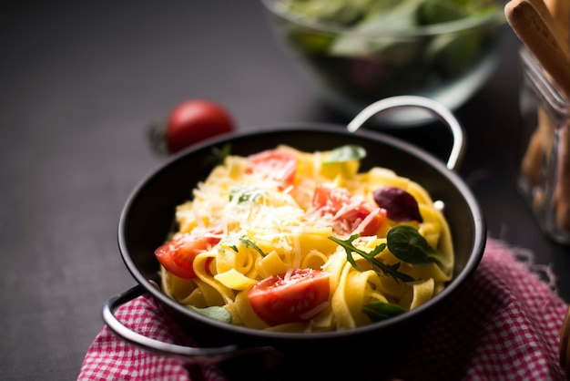 Homemade spaghetti pasta with grated cheese and cherry tomatoes in container Free Photo