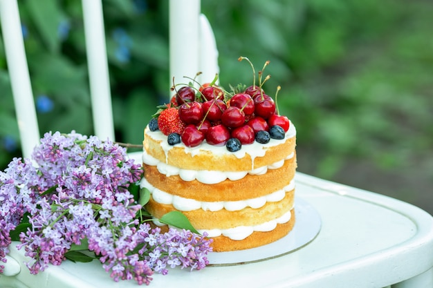 Homemade summer biscuit cake with cream and fresh berries in the garden Premium Photo