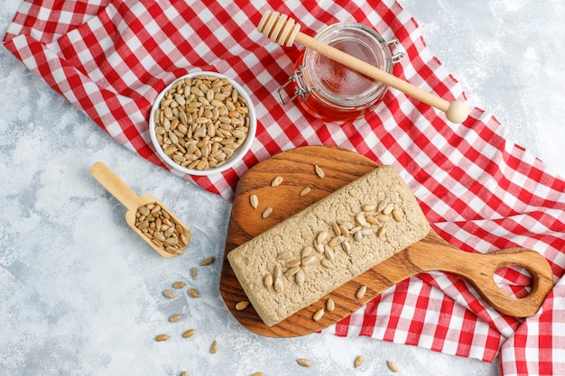 Homemade sunflower halva on cutting board with sunflower seeds Free Photo
