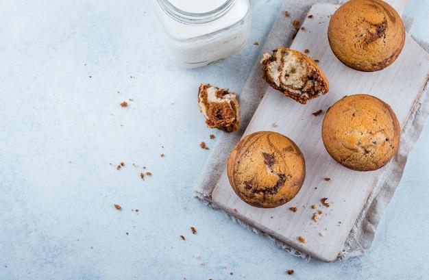 Homemade sweet chocolate vanilla muffins from two types of dough with mason jar of milk Premium Photo