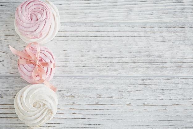 自家製の甘いピンクと白のマシュマロ-軽い木製のテーブルのゼファー。 Premium写真