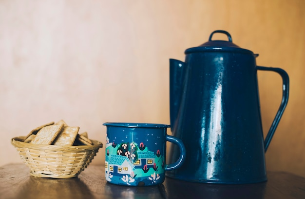 Homemade thin crispy cheesy crackers; mug and porcelain teapot on desk against wall Free Photo