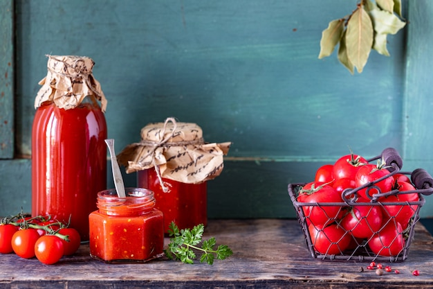 Homemade tomato ketchup made from ripe red tomatoes in glass jars with ingredients on an old wooden table Free Photo