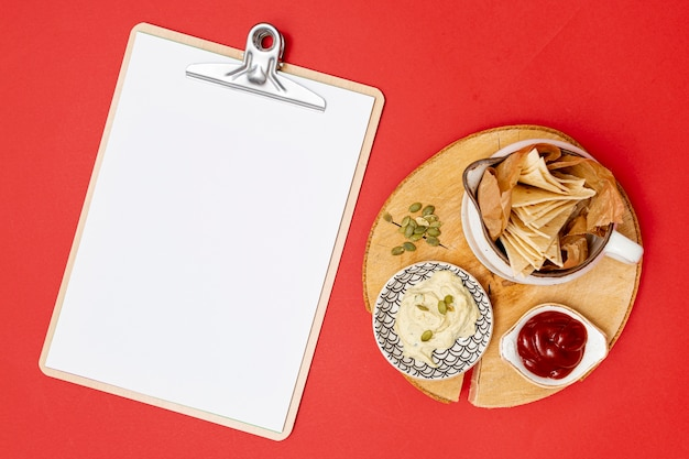Homemade tortilla with dips next to clipboard Free Photo