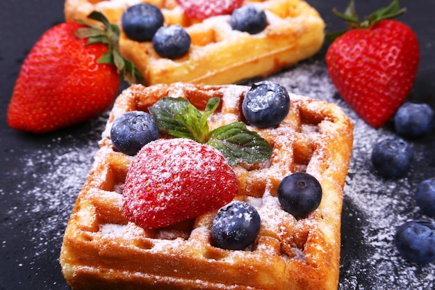 Homemade traditional belgian waffles with fresh fruit, berries and sugar powder on black plate. Premium Photo
