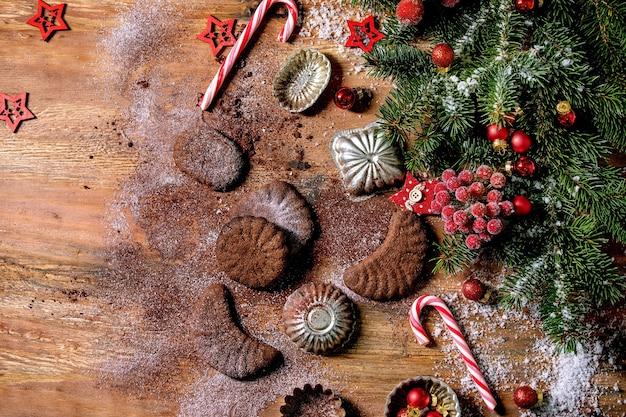 自家製の伝統的なクリスマスショートクラストクッキーチョコレートの三日月形のココア粉砂糖とセラミックプレート、クッキーの型、モミの木、木製の背景に赤いクリスマスの星の装飾 Premium写真