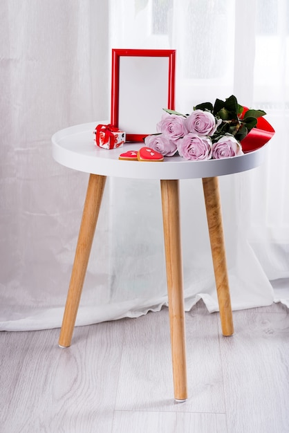 Homemade valentines day heart cookies, pink roses and red frame on white table near floor Premium Photo