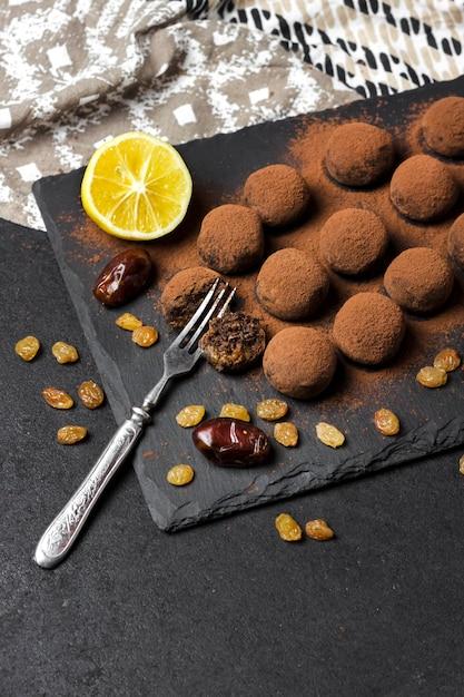 Домашние веганские трюфели с сухофруктами, грецкими орехами и сырым какао-порошком, поданные на черной грифельной тарелке. копировать пространство Premium Фотографии