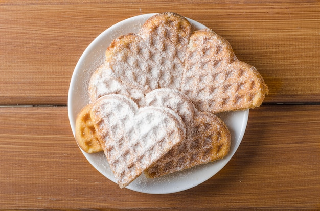 Homemade waffles heart sprinkled with powdered sugar on plate on a wooden table. Premium Photo