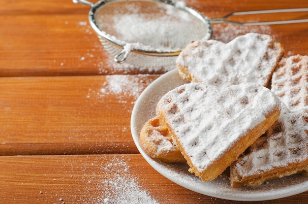 Homemade waffles heart on white plate sprinkled with powdered sugar on a wooden table. Premium Photo
