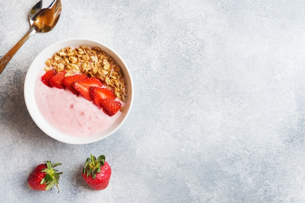 Homemade yogurt with fresh strawberries and muesli. the concept of a healthy breakfast. copy space. Premium Photo