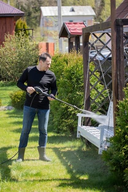 Домовладелец моет белые деревянные качели мойкой высокого давления Premium Фотографии