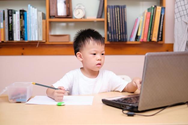 Азиатский ребенок школьника используя портативный компьютер изучая во время его онлайн урока дома, дистанционное обучение, концепция homeschooling Premium Фотографии