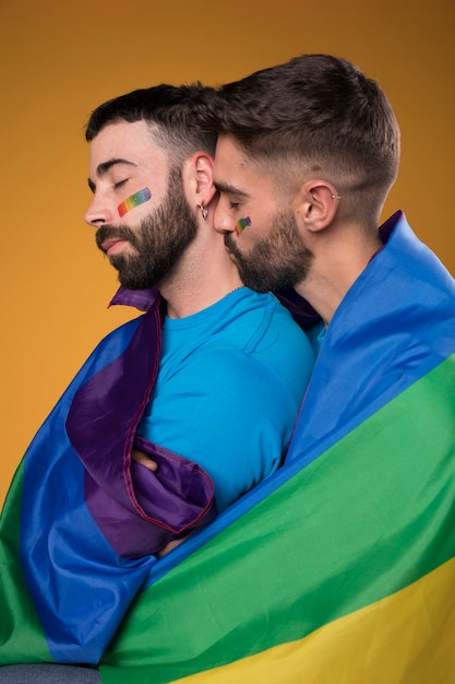 Homosexual couple lovingly hugging wrapped in rainbow flag Free Photo