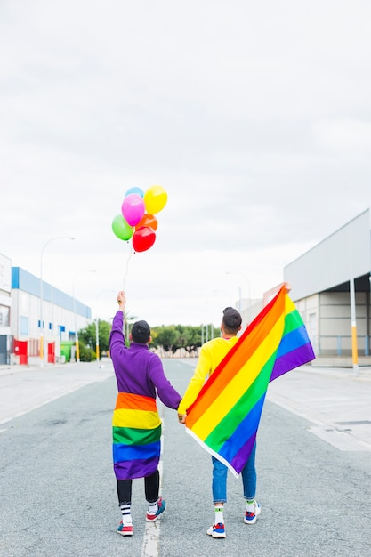 Homosexual couple walking along road holding balloons and lgbt flags Free Photo