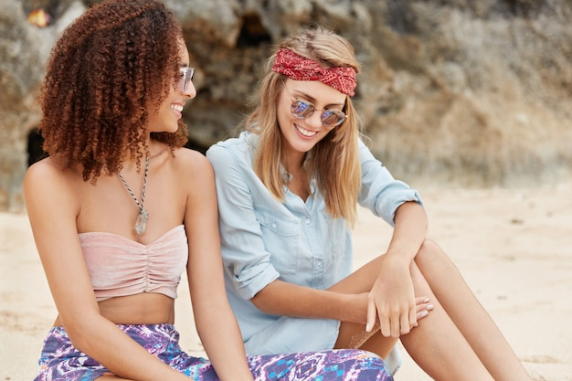 Homosexual family sit next to each other, have pleasant talk, plan their actions on coming weekends, spend spare time at beach against cliff. multiethnic women couple have fun outdoor together Free Photo