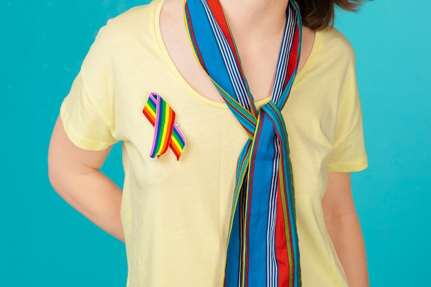 Homosexual and lgbt concept - close up of woman wearing gay pride awareness ribbon on her chest Premium Photo
