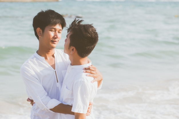 Homosexual portrait young asian couple standing hug together on beach. Premium Photo