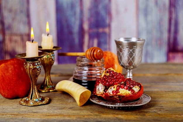 Honey, apple and pomegranate on wooden table over bokeh background Premium Photo