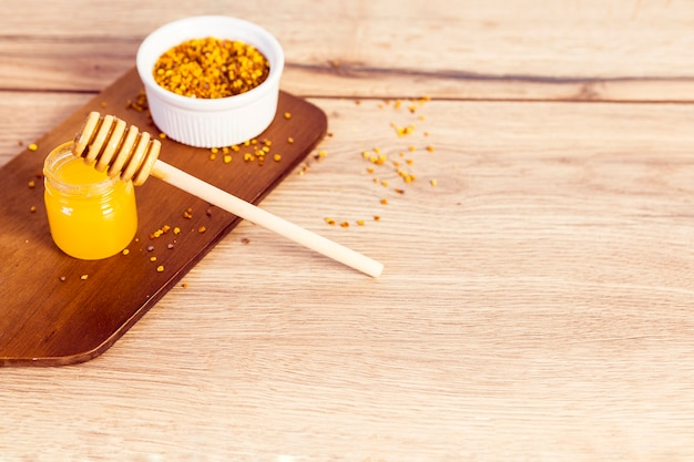Honey and bee pollen on wooden textured Free Photo