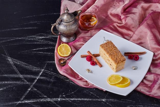 お茶の横にある白い皿にシナモンとフルーツのハニーケーキ。 無料写真