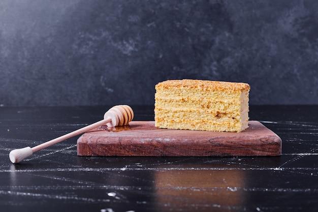 Torta di miele con cannella e frutta sulla zolla bianca accanto al tè. Foto Gratuite