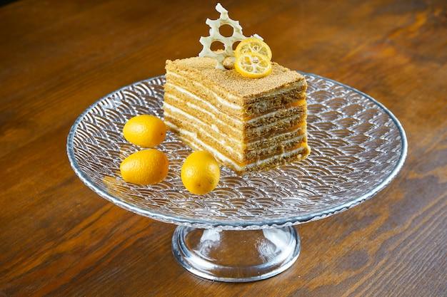 層とペストリークリームと木製のテーブルの透明板に蜂蜜ケーキ。おいしいメドビクケーキのスライス。閉じる。おいしいパン屋のコンセプトです。 Premium写真