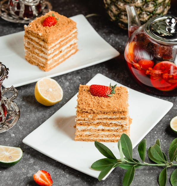 Honey cake with strawberries on it on a white plate Free Photo
