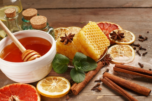 Honey, cinnamon and dried fruits on a wooden table. healthy eating. Premium Photo