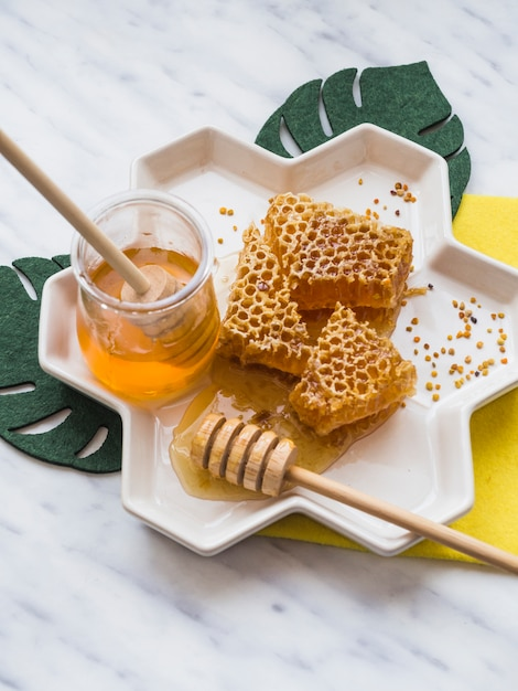 Honey dipper and honey comb with bee pollens in white tray on marble backdrop Free Photo