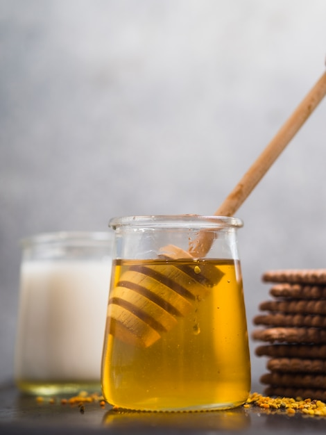 Honey dipper in the honey pot with biscuits against gray background Free Photo