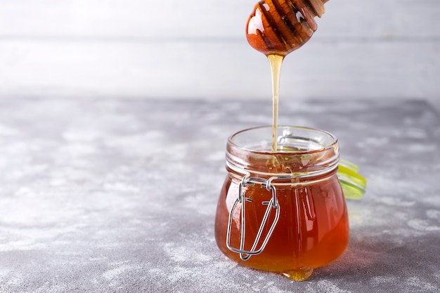 Honey drip in jar on the table Premium Photo