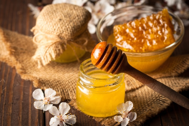 Honey dripping from a wooden honey dipper in a jar on wooden grey rustic Premium Photo