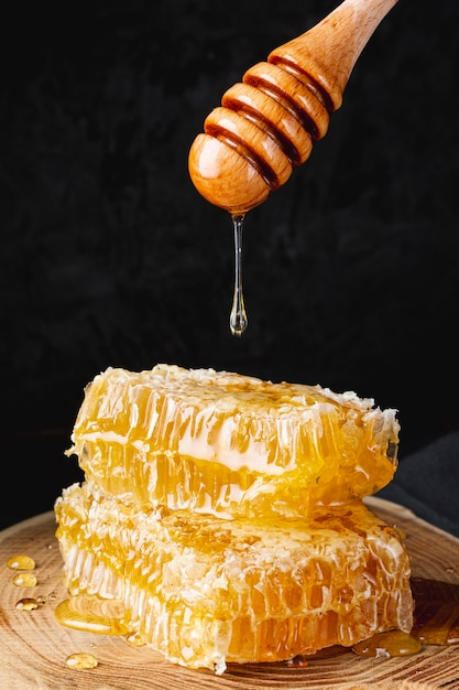 Honey dripping off dipper over honneycombs Free Photo