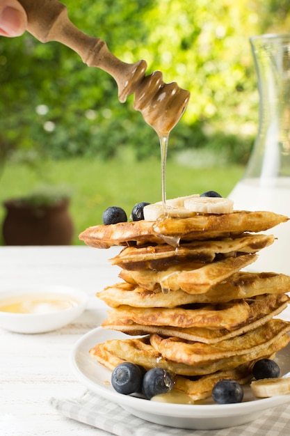 Honey falling on waffle tower Free Photo