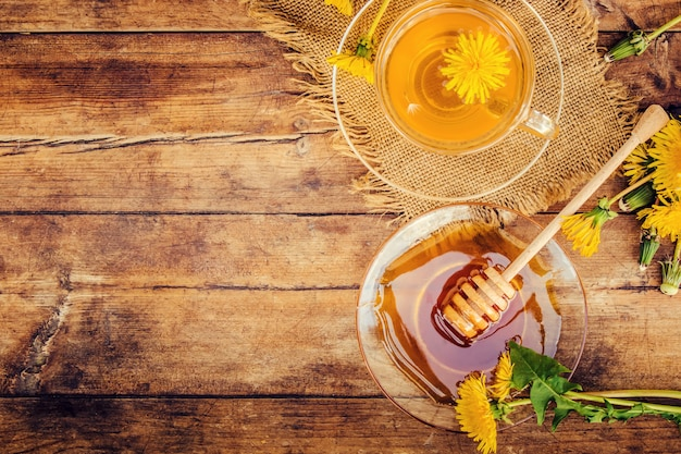 Honey from dandelion and a cup of tea. selective focus. Premium Photo