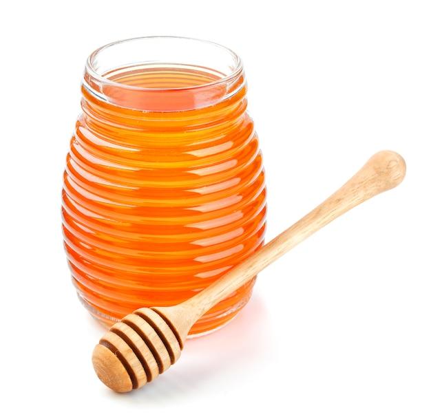 Honey in glass jar isolated on white background Premium Photo