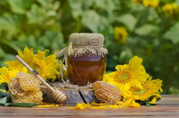 Honey in glass jar with bee flying Premium Photo