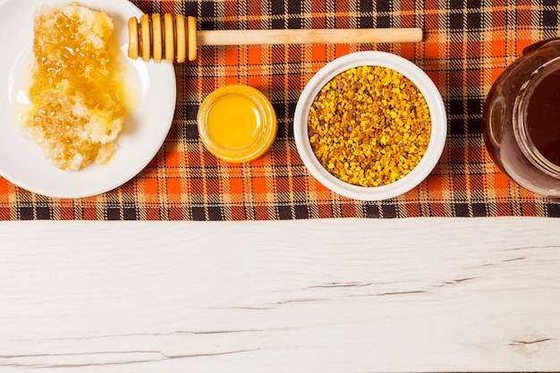 Honey; honeycomb and bee pollen arranged in a row on table cloth Free Photo