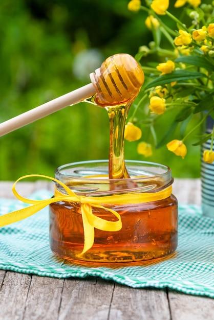 Мед в стеклянной банке с цветами Premium Фотографии