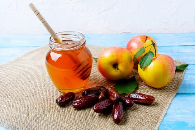 Honey jar, dates and apples on burlap napkin Premium Photo