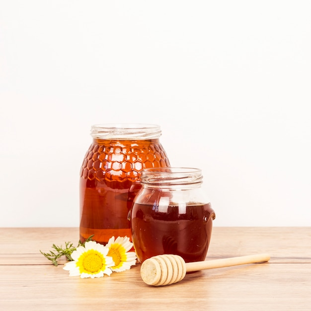 Honey jar and honey dipper with white flower over wooden surface Free Photo